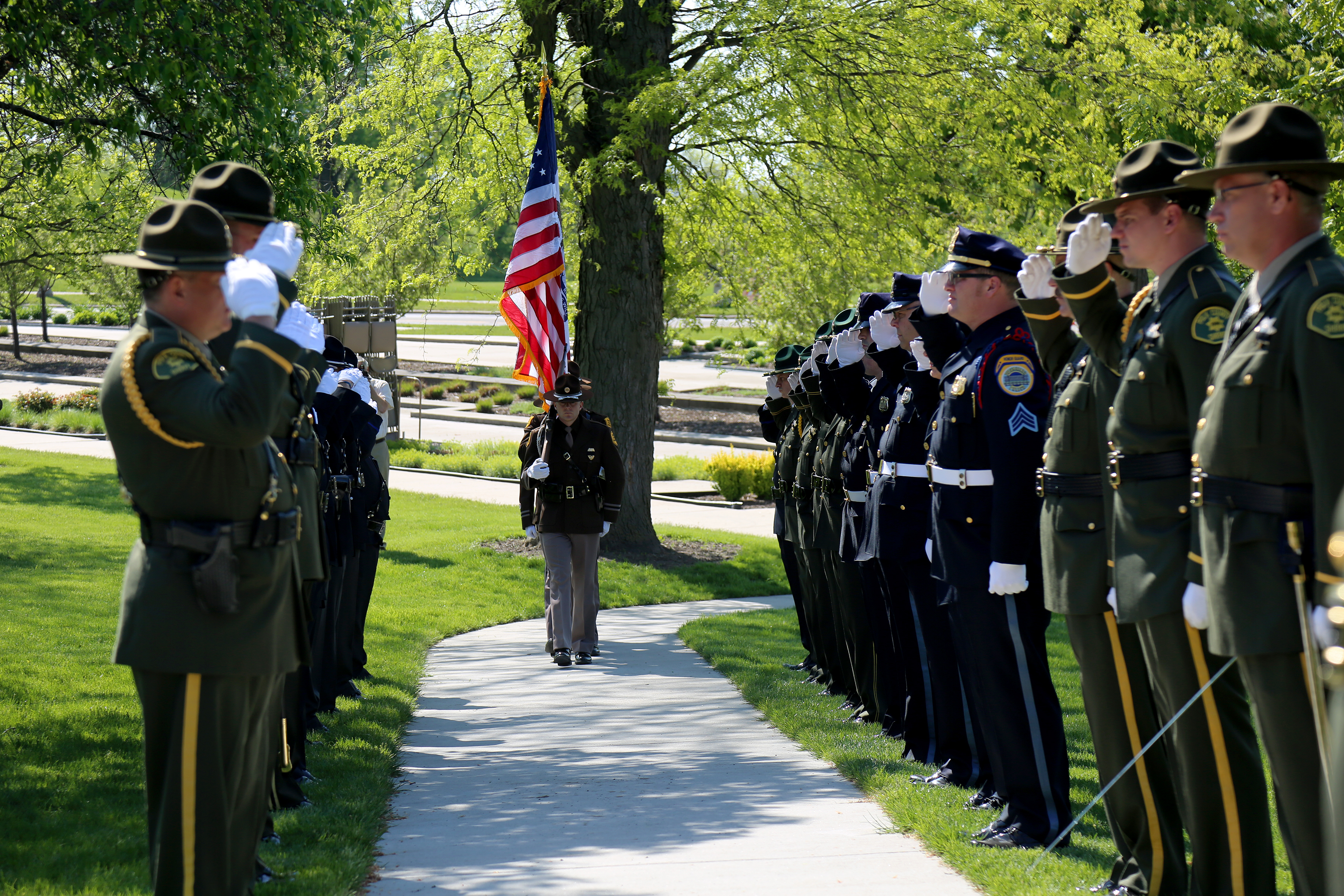Sidewalk lined with law enforcement as Iowa State Patrol Color Guard walks to memorial.