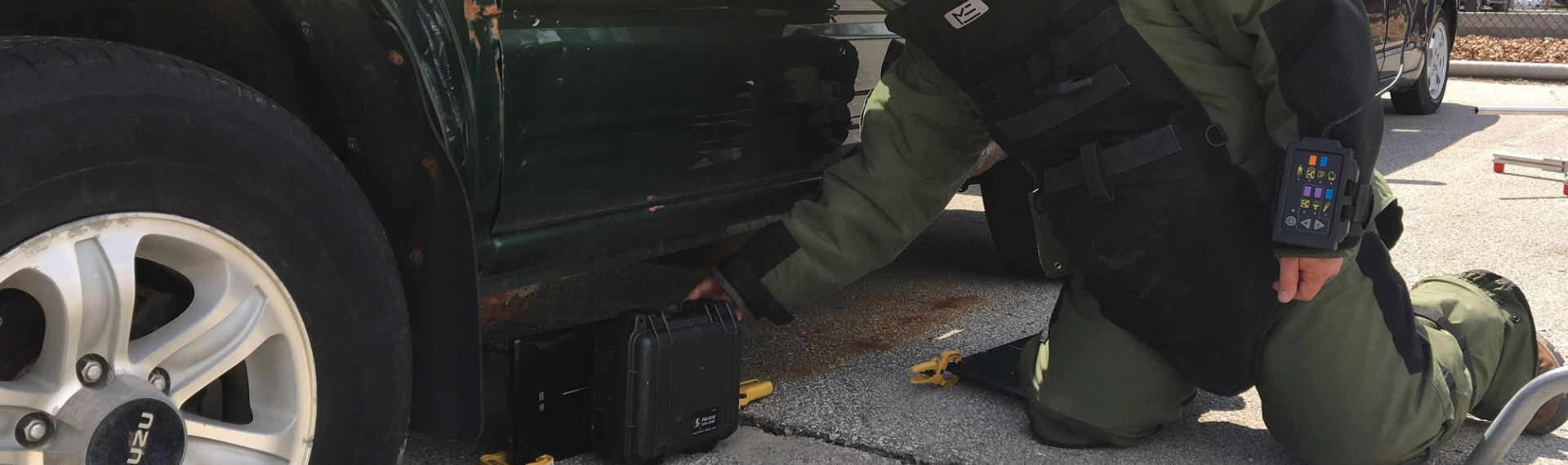 Special agent in bomb suit with portable xray machine and suspicious package under a vehicle.
