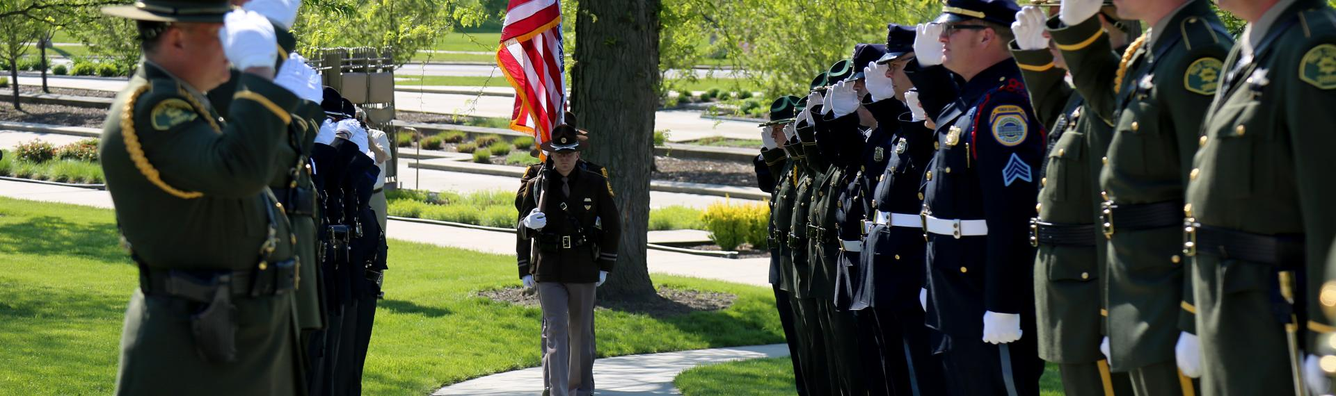 Photo of Iowa State Patrol Honor Guard marching up the sidewalk lined with Iowa law enforcement officers to the Peace Officer Memorial during a ceremony.