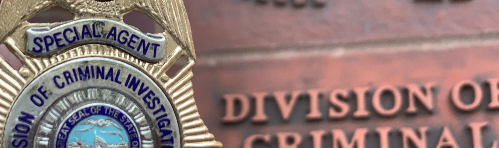 DCI badge with DCI wall signage in background that says Division of Criminal Investigation.