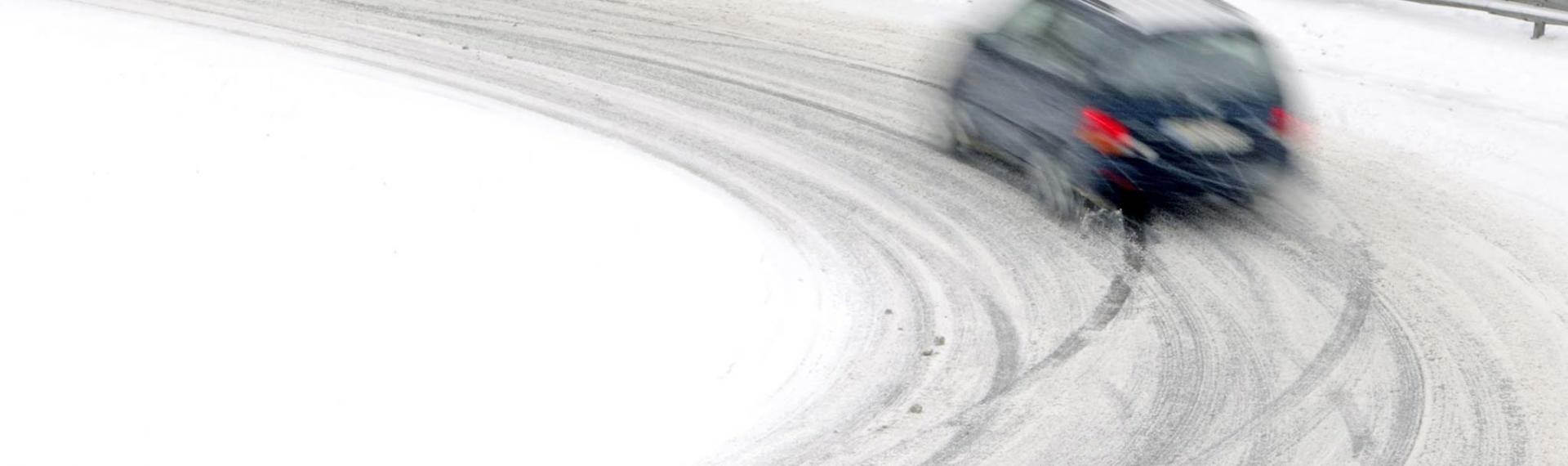 Car driving on snowy road.